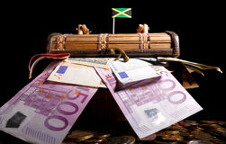 Jamaican flag on top of crate. Full of money stock photography