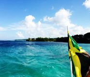 Jamaican Flag trailing boat in the Ocean. Jamaican Flag trailing a boat in the Ocean near Montego Bay Jamaica stock photo