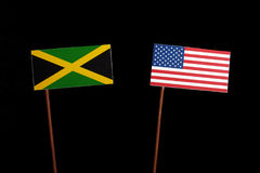 Jamaican flag with USA flag on black. Background stock photo