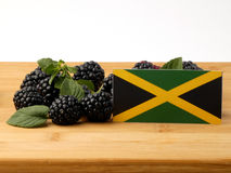 Jamaican flag on a wooden panel with blackberries isolated on a. White background stock photo