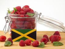 Jamaican flag on a wooden panel with raspberries isolated on a w. Hite background stock photo