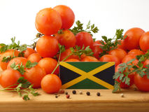 Jamaican flag on a wooden panel with tomatoes isolated on a whit. E background royalty free stock image