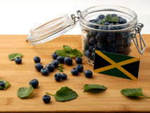 Jamaican flag on a wooden plank with blueberries on whi. Te stock photo