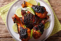 Jamaican food: jerk chicken drumstick with lime closeup on a plate. horizontal top view from above. Jamaican food: jerk chicken drumstick with lime closeup on a royalty free stock photo