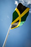 Jamaican JAMAICA flag. Black green and Gold Jamaican flag in wind on flagpole stock image