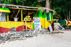 Jamaican man serving soup cooking on open fire pot in traditional outdoor beach vendor cook shop royalty free stock images