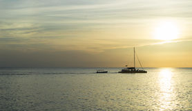 Jamaican sunset. A Jamaican sunset outlining a sailing boat Royalty Free Stock Photo
