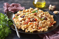 Jambalaya - spicy rice with meat and vegetables. Jambalaya - spicy rice with meat and vegetables on a black plate on a dark rustic metal,slate or stone stock photos