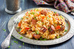 Jambalaya. Spicy rice with smoked sausage and red pepper. On a round metal tray Stock Photo