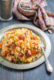 Jambalaya. Spicy rice with smoked sausage and red pepper. On a round metal tray Royalty Free Stock Images