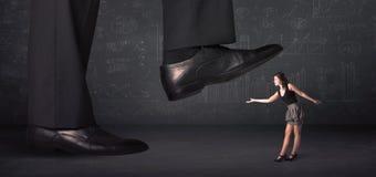 Jambe énorme faisant un pas sur un concept minuscule de businnesswoman Photo libre de droits