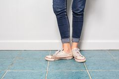 Jambe asiatique de fille avec la mode de treillis avec de vieilles chaussures Image libre de droits