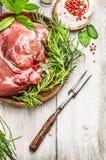 Jambe d'agneau avec la fourchette de viande et d'assaisonnement frais sur le fond en bois rustique Photographie stock libre de droits