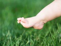 Jambe de bébé faisant la première étape sur l'herbe verte pied nu de bébé d'ittle image stock