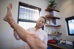 Jambe de examen de docteur féminin du patient masculin Images stock