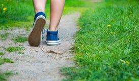 Jambe de marche de femmes dans des chaussures d'espadrille de jeans sur la route Photos stock