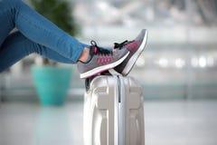 Jambe de passager sur le bagage à l'aéroport Image stock
