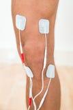 Jambe de personne avec des électrodes sur le genou Photo libre de droits