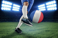 Jambe donnant un coup de pied le ballon de football dans le stade Photo stock