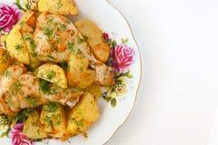 Jambe et pommes de terre rôties de poulet du plat blanc Photos stock