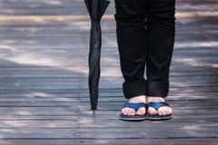Jambe seul de support de port de sandale de jeune femme sur le pont en bois h photos stock