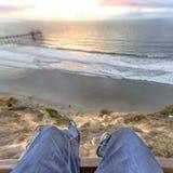 Jambes accrochant outre du bord d'un bâtiment avec les vues d'océan et de pilier du coucher du soleil Photos libres de droits