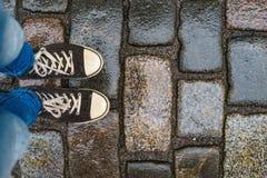 Jambes adolescentes dans des espadrilles sur le trottoir humide Photo stock