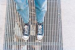 Jambes adolescentes utilisant des espadrilles de denim des fleurs, se tenant sur une grille de rue Style de hippie de rue Photographie stock