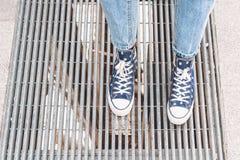 Jambes adolescentes utilisant des espadrilles de denim des fleurs, se tenant sur une grille de rue Style de hippie de rue Images libres de droits