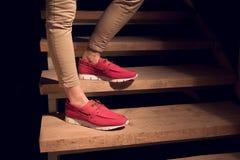 Jambes avec des mocassins d'un cuir de rouge sur escaliers Images libres de droits