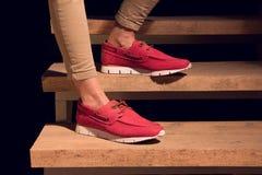 Jambes avec des mocassins d'un cuir de rouge sur escaliers Photo libre de droits
