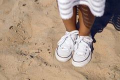 Jambes bronzées dans des espadrilles se tenant sur le sable Photos libres de droits