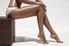 Jambes bronzages de belle femme. Contre le mur blanc. Image stock