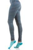 Jambes convenables de femme portant les pantalons rayés colorés et les chaussettes bleues de la vue de côté dans la position sur  Photographie stock libre de droits