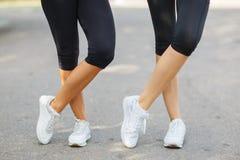 Jambes convenables de plan rapproché dans les vêtements de sport sur un fond brouillé Filles dans des espadrilles Concept de cour Photo stock