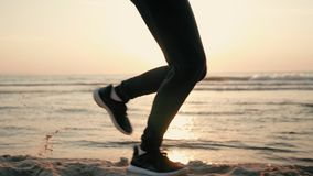 Jambes courantes de femme pulsant au coucher du soleil à la plage de côte avec la fusée de lentille de Sun banque de vidéos