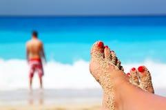 Jambes croisées sur la plage Image stock