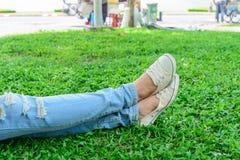Jambes cultivées de femme en denim avec les espadrilles blanches se reposant sur l'herbe Photos stock
