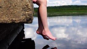 Jambes décontractées au-dessus de l'eau de lac banque de vidéos