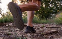 Jambes d'homme fonctionnant sur la traînée dans les montagnes photographie stock libre de droits