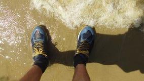 Jambes d'hommes dans des espadrilles L'homme se tient sur le repos de déplacement d'espadrilles humides de vagues de sable de bor Photos libres de droits