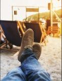 Jambes d'hommes dans des espadrilles sur le fond des chaises longues sur la plage Photographie stock
