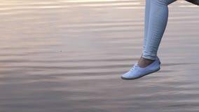 Jambes d'oscillation de femme au-dessus de l'eau calme au coucher du soleil banque de vidéos