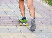 Jambes d'un adolescent montant une planche à roulettes sur le trottoir Image libre de droits