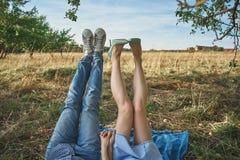 Jambes d'un couple se trouvant sur l'herbe dans le champ de pommiers Images stock