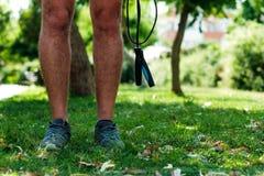 Jambes d'un homme avec la corde de saut Photos stock