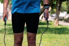 Jambes d'un homme avec la corde de saut Image stock