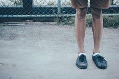 Jambes d'un homme utilisant les chaussures de toile noires et le pantalon brun se tenant sur la terre concrète avec l'espace de c Images libres de droits