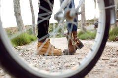 Jambes d'un jeune couple dans l'amour sur le vélo en parc Image stock