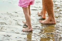 Jambes d'un père et d'un fils sur la plage Photo stock